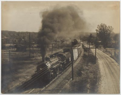 "Photograph of ""Katy Flyer"" rolling down the railroad tracks in Denison, Texas."